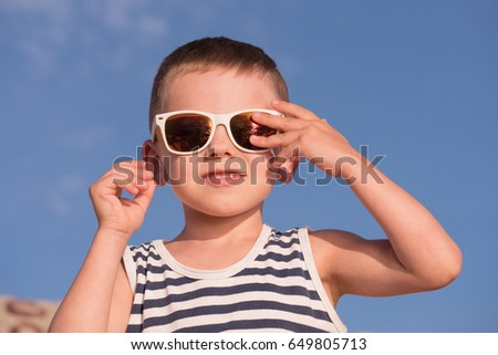 happy little boy wearing sunglasses and striped shirt touching his sunglasses with fingers on blue sky background