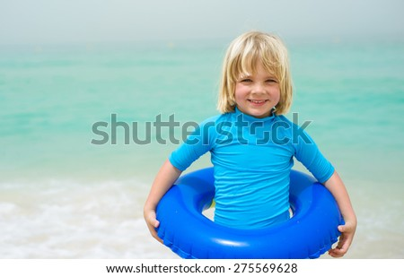 Happy little boy with a floating ring at a tropical beach - stock photo