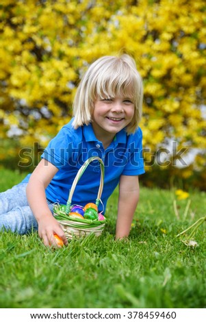Happy  little boy with basket  looking Easter eggs outdoors on a sunny day - stock photo