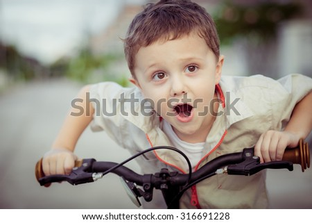 Happy little boy with bicycle at the day time - stock photo