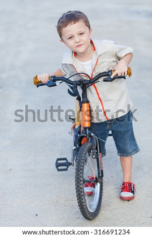 Happy little boy with bicycle standing on road  at the day time - stock photo