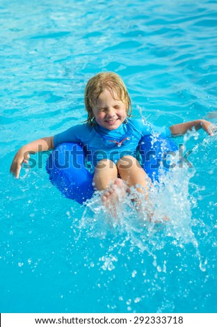 Happy little boy  with blue life ring has fun in the swimming pool