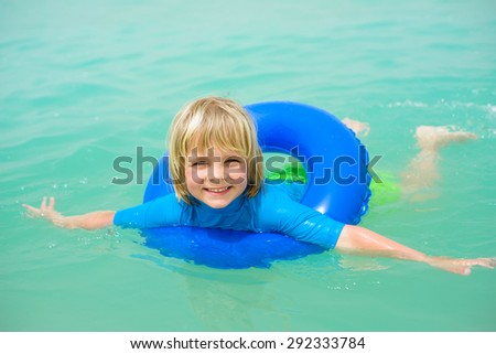 Happy little boy with blue life ring has fun in the water - stock photo