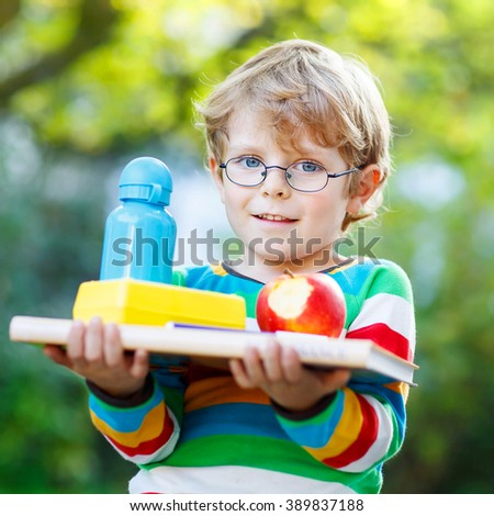 Happy little boy with books, apple and drink bottle on his first day to elementary school or nursery. Outdoors.  Back to school, kids, lifestyle concept - stock photo