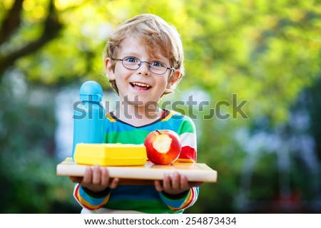 Happy little boy with books, apple and drink bottle on his first day to school or nursery. Outdoors, Back to school concept - stock photo