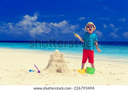 happy little boy with built sandcastle on tropical beach - stock photo