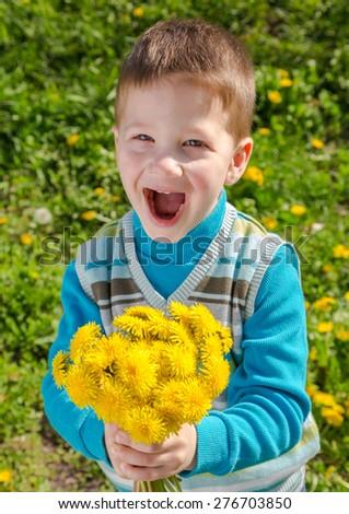 Happy Little boy with bunch of dandelions on green field - stock photo