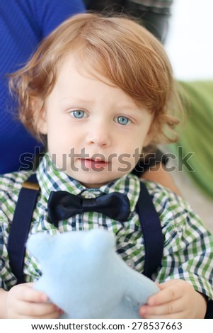 Happy little boy with curly hair holds soft toy. Close up view