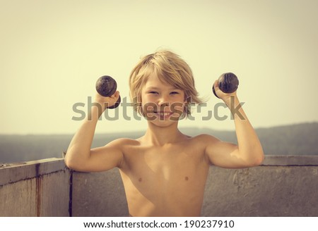 Happy little boy with dumbbells doing exercises in the loggia. - stock photo