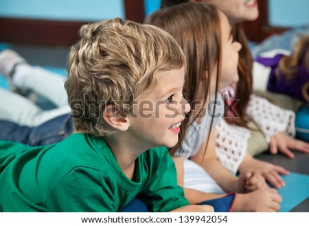 Happy little boy with female friends lying on floor in kindergarten - stock photo