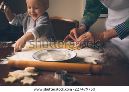Happy little boy with grandmother cutting  Christmas cookies. - stock photo