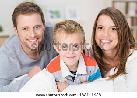 Happy little boy with his smiling young parents posing together in their home sitting on a sofa looking at the camera with warm friendly smiles - stock photo