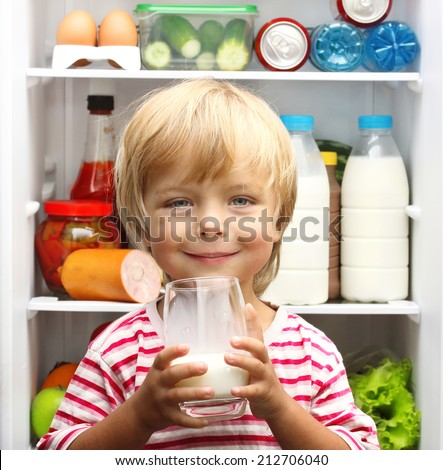 Happy little boy with milk against refrigerator with food - stock photo