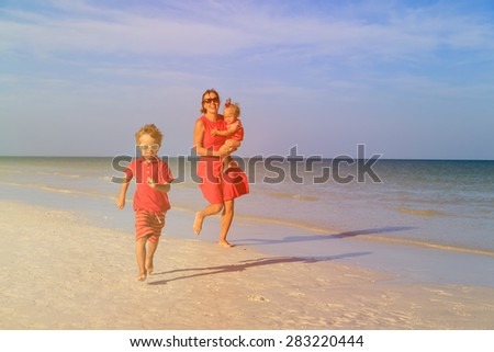 happy little boy with mother and sister running on summer beach
