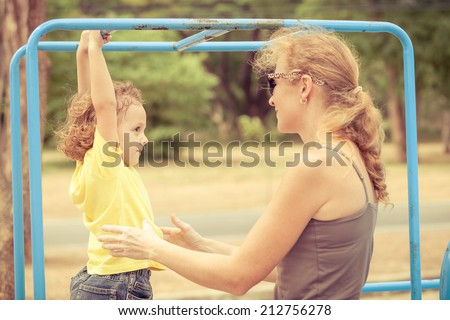 Happy little boy with mother on the playground at the day time - stock photo