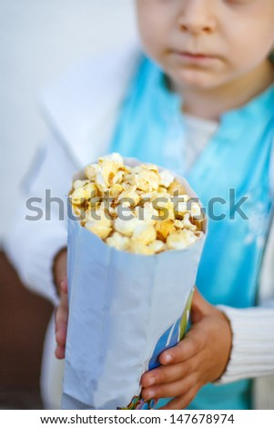Happy little boy with popcorn bag, eating sweets. Selective focus on popcorn bag - stock photo