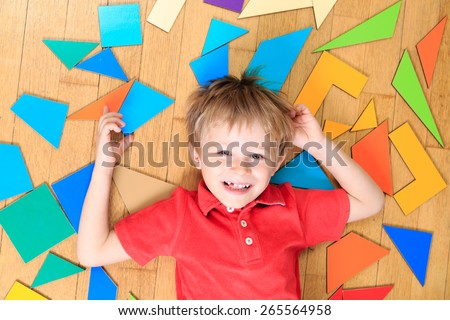 happy little boy with puzzle toys on wooden floor, early learning - stock photo