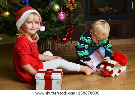 happy little boy with sister near Christmas tree - stock photo
