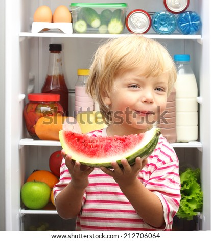 Happy little boy with watermelon against refrigerator with food - stock photo