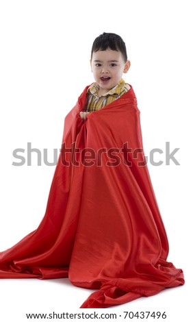 happy little boy wrapped in red silk fabric, isolated on white background - stock photo