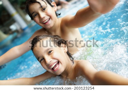 Happy little boys enjoying relaxing and splashing in water - stock photo