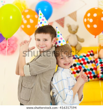 Happy little boys having fun at birthday party