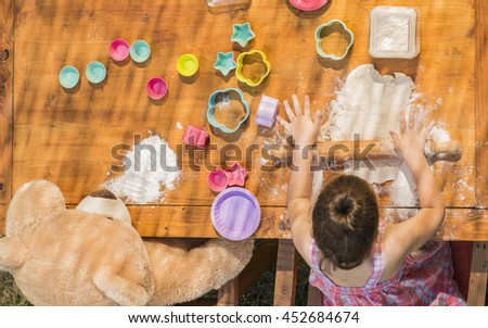 Happy little chef girl and teddy bear smeary with flour baking and having fun playing with dough outdoor, seen from above. Kid playing with dough and teddy bear outdoor in backyard kitchen - stock photo