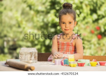 Happy little chef girl playing in outdoor kitchen with dough, flour and pastry utensils. Little Girl Baking Cookies - stock photo