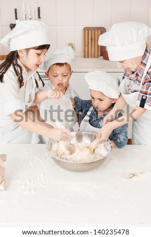 happy little chefs preparing dough in the kitchen - stock photo