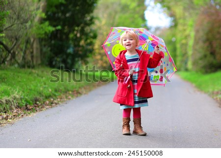 Happy little child, adorable blonde curly toddler girl wearing red duffle coat and holding colorful umbrella walking in the forest or park on a sunny warm spring or autumn day