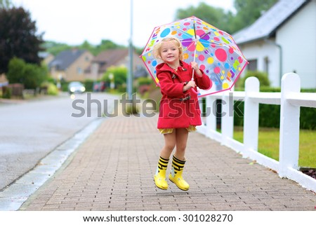 Happy little child, adorable blonde curly toddler girl, wearing red duffle coat, bright yellow wellies and holding colorful umbrella jumping on the street on a chilly autumn or spring day - stock photo