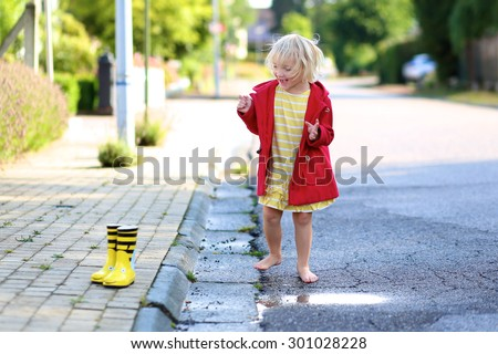 Happy little child, adorable blonde curly toddler girl, wearing red duffle coat enjoying sun after rain running barefoot and jumping on the puddle on the street on a sunny autumn or spring day - stock photo