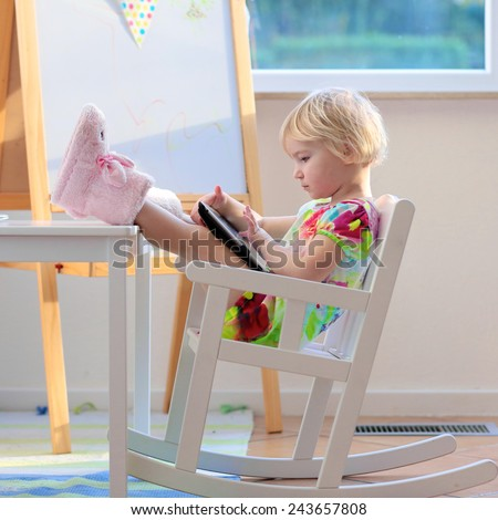 Happy little child, adorable blonde toddler girl enjoying modern generation technologies playing with tablet pc sitting comfortable indoors on a white rocking chair with her feet on the table - stock photo