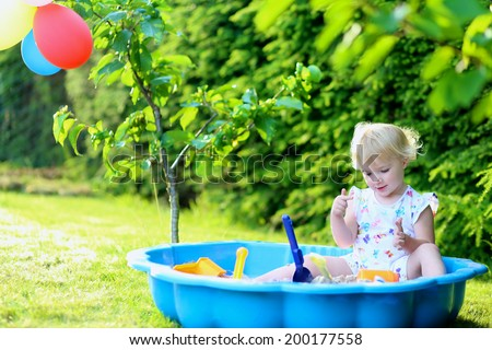 Happy little child, adorable blonde toddler girl having fun playing outdoors in party decorated garden with plastic toys sitting in blue sand box celebrating her birthday on a sunny summer day - stock photo