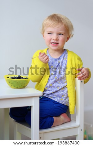 Happy little child, adorable blonde toddler girl, having healthy snack eating blueberries sitting indoors at small white table - stock photo