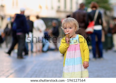 Happy little child, adorable blonde toddler girl in beautiful dress, walking on crowded touristic street in the center of the city eating ice-cream on a sunny summer evening, Brussels, Belgium - stock photo