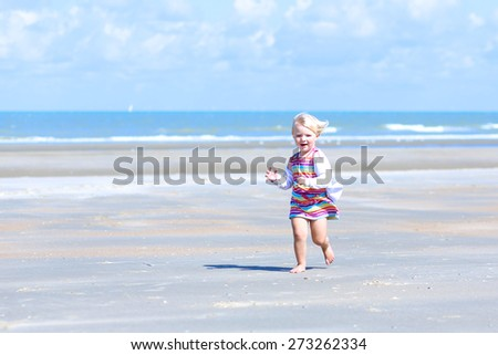Happy little child, adorable blonde toddler girl, playing and running on the beautiful peaceful sandy beach at the North sea - stock photo