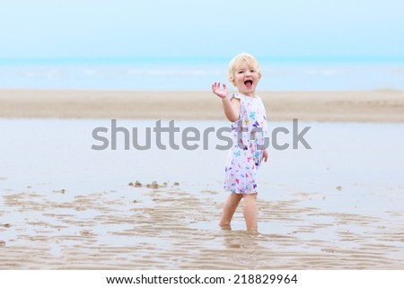 Happy little child, adorable blonde toddler girl, playing, dancing and running on the beautiful peaceful sandy beach at the sea - stock photo