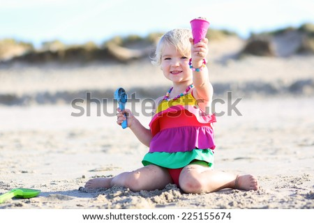 Happy little child, adorable blonde toddler girl wearing colorful necklace playing on the beach at North Sea making sandy ice cream with plastic toys - stock photo