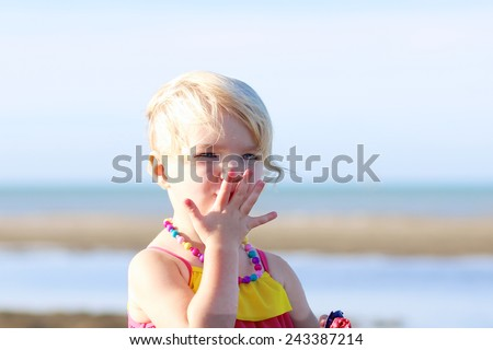 Happy little child, adorable blonde toddler girl wearing colorful necklace playing on the beach at North Sea - stock photo