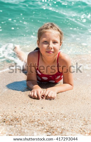 Happy little child, adorable blonde toddler girl wearing colorful swimsuit on the beach Azov Sea  - stock photo