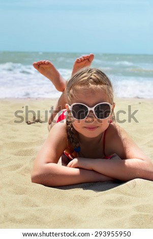 Happy little child, adorable blonde toddler girl wearing colorful swimsuit playing on the beach Azov Sea making ice cream from sand using plastic toys - stock photo