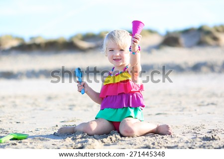Happy little child, adorable blonde toddler girl wearing colorful swimsuit playing on the beach at North Sea making ice cream cone from sand using plastic toys - stock photo