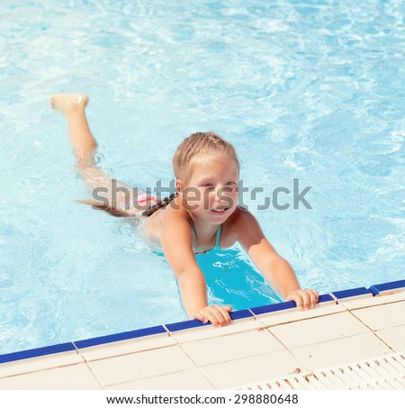 Happy little child, adorable blonde toddler girl wearing colorful swimsuit sits on the edge of the pool - stock photo