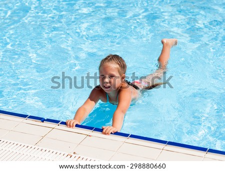 Happy little child, adorable blonde toddler girl wearing colorful swimsuit sits on the edge of the pool