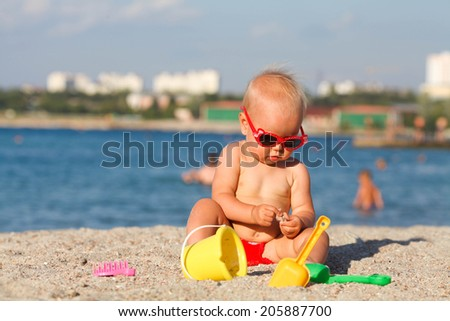 Happy little child, adorable blonde toddler  playing on the beach with toys - stock photo