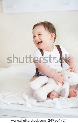 Happy little child, baby boy laughing and playing with his teddy bear - stock photo
