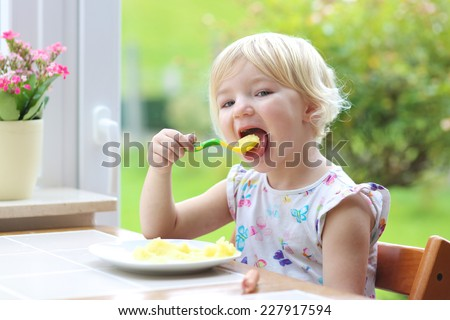 Happy little child, blonde curly toddler girl, enjoying healthy lunch eating mashed potatoes with sausage sitting in high chair at bright sunny kitchen next to big garden view window - stock photo