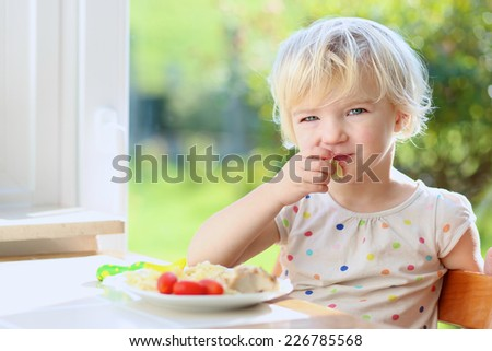 Happy little child, blonde curly toddler girl, enjoying healthy lunch eating pasta with tomatoes sitting in high chair at bright sunny kitchen next to big garden view window - stock photo