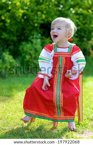 Happy little child, blonde curly toddler girl in traditional russian dress playing outdoors in the garden sitting on small wooden chair